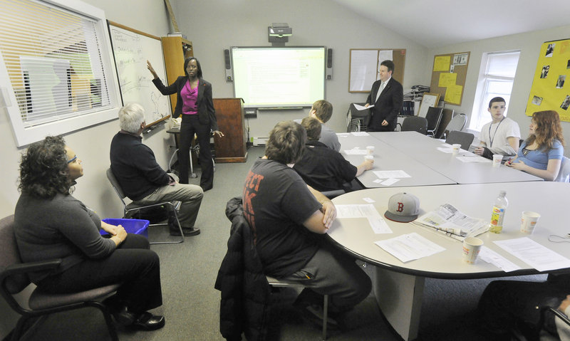 Bank employee Carine Rugema Stubbs teaches financial literacy classes at Youth Building Alternatives, operated by Learning Works in Portland, on Tuesday.