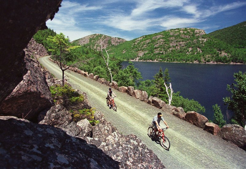 Bicyclists glide past a vista overlooking Jordan Pond and the Bubbles Mountains on a carriage road at Acadia National Park, near Bar Harbor.