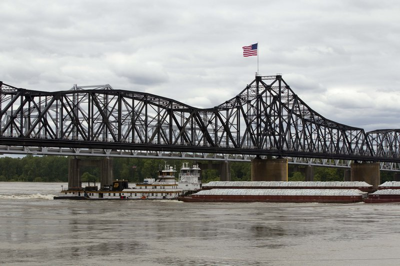 Several boats push cargo barges up the Mississippi River in Vicksburg, Miss., on Monday. The Coast Guard reopened the swollen Mississippi River north of New Orleans on Tuesday.
