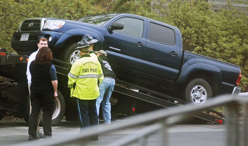 Massachusetts State Police officers stand by Wednesday as a Toyota Tacoma driven by Julianne McCrery is placed on a tow truck in a rest area along I-495 in Chelmsford, Mass.