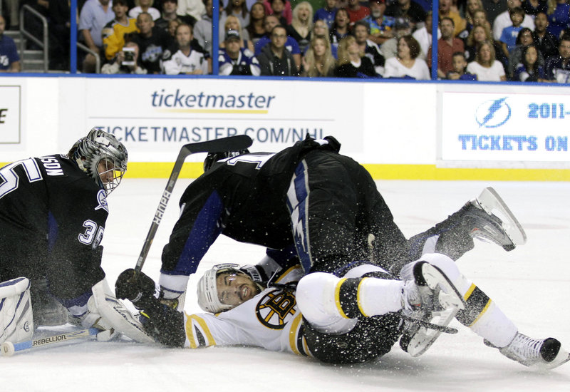 Dominic Moore of the Tampa Bay Lightning lands atop Chris Kelly of Boston in front of Lightning goalie Dwayne Roloson during the Bruins' 2-0 victory Thursday night.