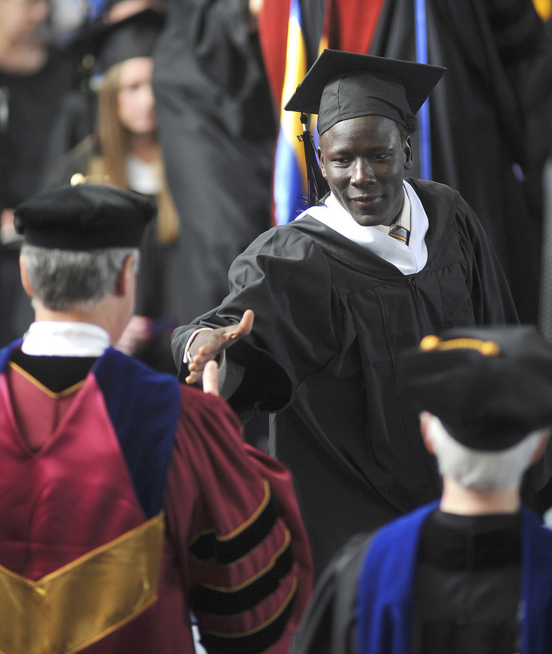 A Saint Joseph's College graduate reaches for the hand of President Joe Lee during commencement excercises in Standish last week.