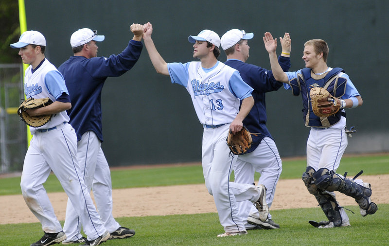 Westbrook pitcher Scott Heath, center, and his brother, catcher Kyle Heath, celebrate after the final out Saturday as the unbeaten Blue Blazes downed Deering 6-0 at Hadlock Field.