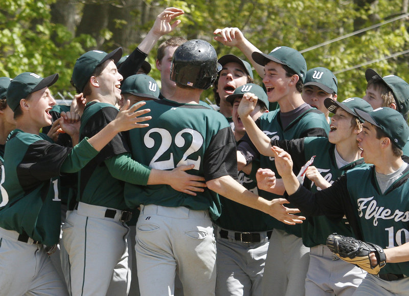 Mitch Newlin of Waynflete is welcomed by his teammates Saturday after hitting a two-run homer in the second inning of the second game against North Yarmouth Academy. NYA won 14-8 after Waynflete won the opener, 3-2. Newlin drove in six runs in the doubleheader.