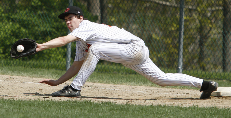 Ryan Salerno, the first baseman for North Yarmouth Academy, keeps his foot on the base and makes the stretch to record a second-inning out in the second game of the doubleheader against Waynflete.