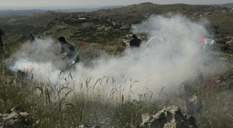 Palestinians run from tear gas fired by Israeli soldiers during a demonstration against Jewish settlements in the northern West Bank village of Iraq Burin on Saturday. The settlement issue has been a stumbling block to resuming negotiations.