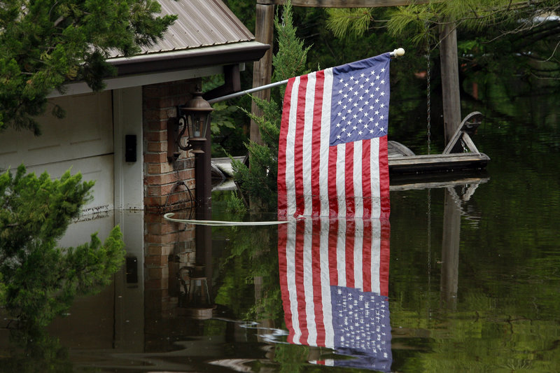 """A U.S. flag reflects off the Mississippi River floodwaters in Vicksburg, Miss., on Friday. """"We will come HOME,"""" said one sign in a Louisiana town."""