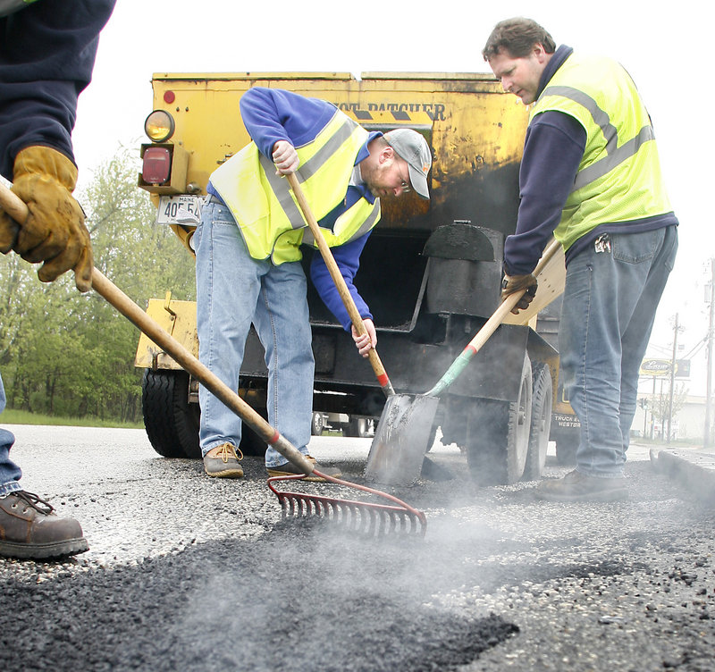 Steam rises as Ray Routhier, center, and city worker Brian Parent fill in one of the many Portland potholes.
