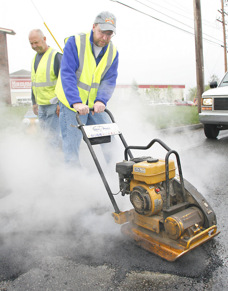 Reporter Ray Routhier uses a heavy compactor to flatten pavement patch as Kim Dolbow, a Portland Public Services Department maintenance worker, oversees his work.