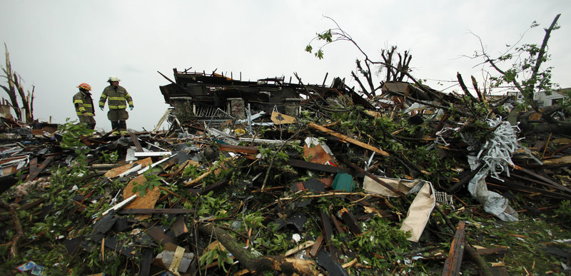 Firefighters on Monday search the rubble of a home destroyed by Sunday's tornado in Joplin, Mo., that left at least 116 people dead.