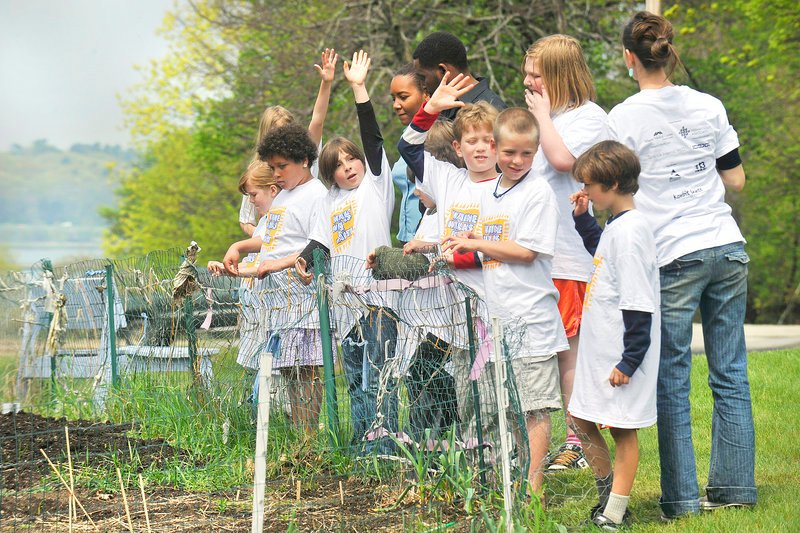 """Fourth-grade students at the Friends School of Portland and their teacher show their school's garden to their Haitian visitors during a tour May 24. The """"Maine Walks for Haiti"""" fundraiser will be held Saturday around Back Cove."""