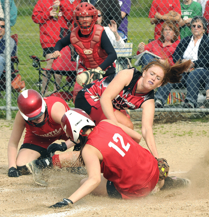 Stephanie McDonough scores for South Portland as Scarborough pitcher Mo Hannan applies a tag Tuesday. McDonough scored after a throw home got away in an attempt to get Libby Grant, left, who scored first.