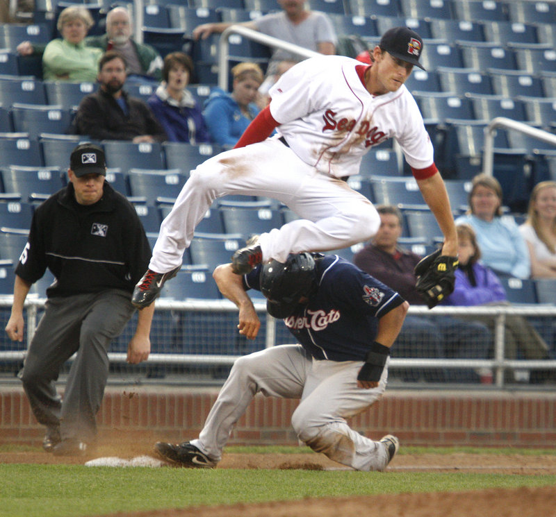 Sea Dogs third baseman Will Middlebrooks snares a high throw as Craig Stansberry of the Fisher Cats slides in with a stolen base Tuesday night at Hadlock Field.