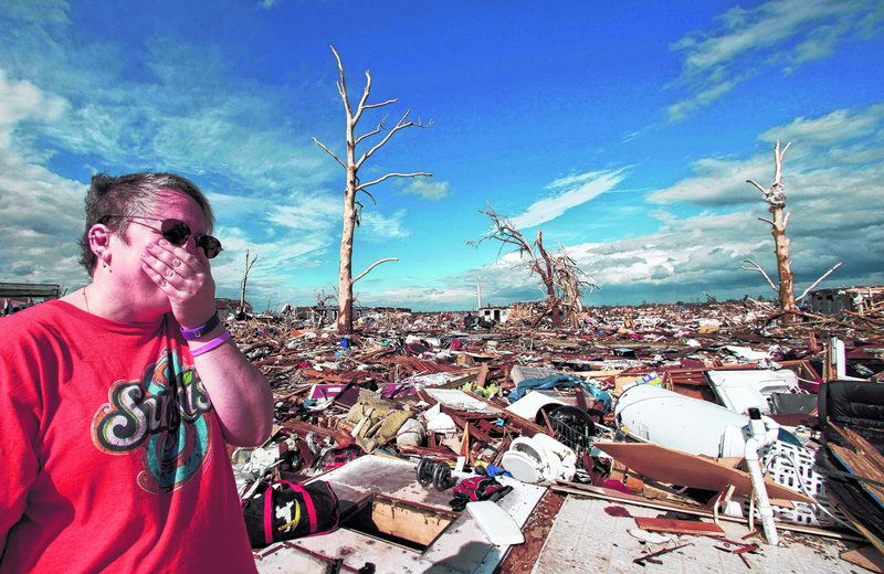 The Associated Press Debra Younger surveys her sons' home in Joplin, Mo., on Wednesday. Six people in the house, including her son, escaped major injuries by huddling in the bathroom of the home, which was blown away. The EF-5 tornado tore through much of the city Sunday.