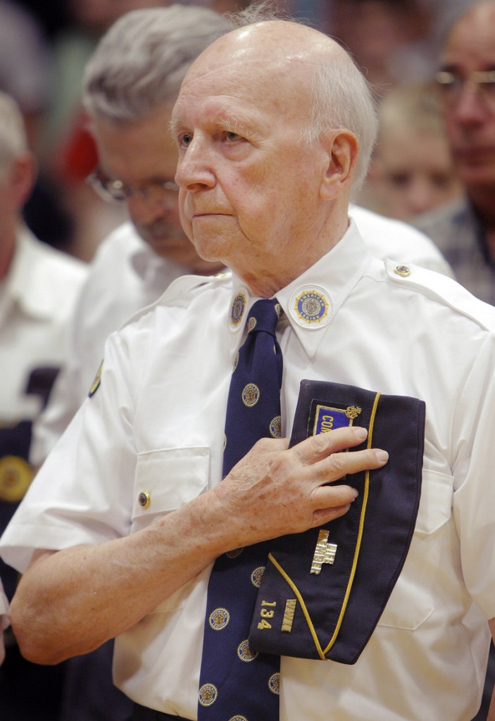 Gerald Burggren of Alfred, a Navy veteran from World War II, holds his cap over his heart during the playing of taps at Massabesic High School on Thursday.
