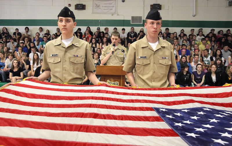 Tony Coburn, left, and Alex Storey perform a flag-folding ceremony Thursday with other Navy Junior Reserve Officer Training Corps cadets at Massabesic High School. Behind them is Daniel Mills, a NJROTC cadet who emceed the assembly.