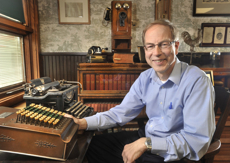 """Peter Geiger sits with equipment, books, almanacs and other memorabilia at the company's headquarters in Lewiston. One of his favorites is the """"Guide to Kissing"""" almanac from the 1890s."""