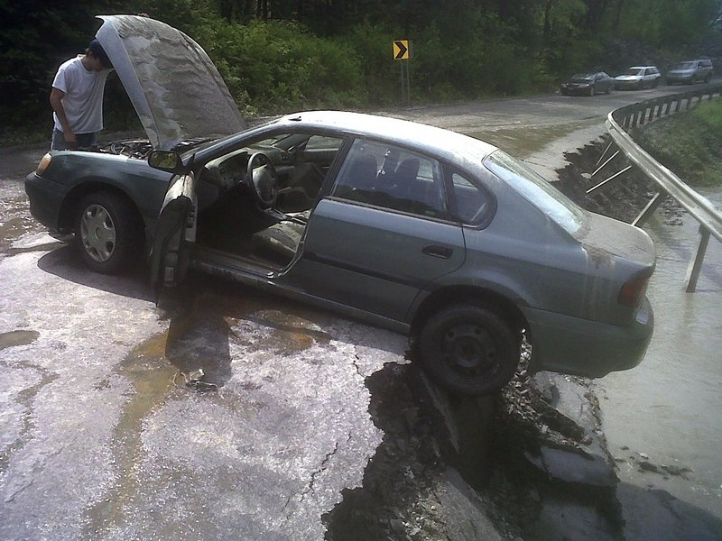Adam Cooley of Barre, Vt., checks the damage to the engine of his 2001 Subaru Legacy in Barre Town, Vt. Flash floods triggered by thunderstorms roared through central Vermont on Friday.