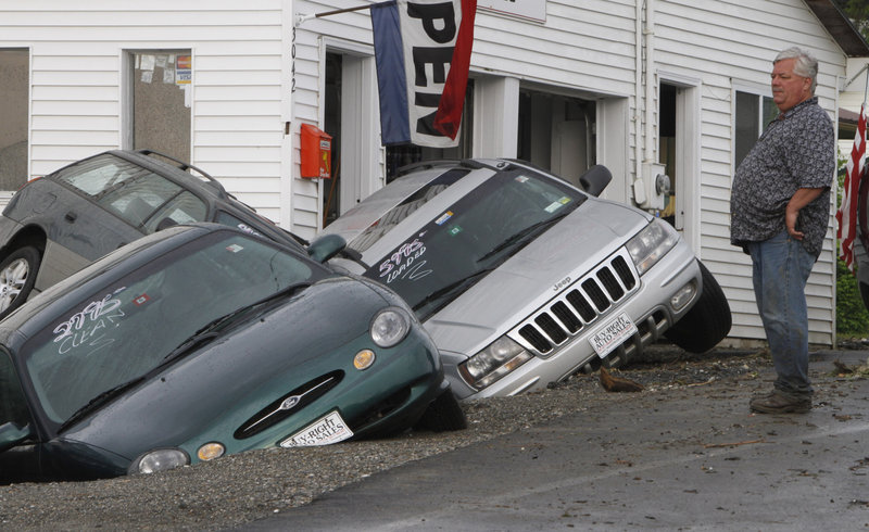 Rene Crete looks over damaged cars at Buy Right Auto in East Montpelier, Vt.