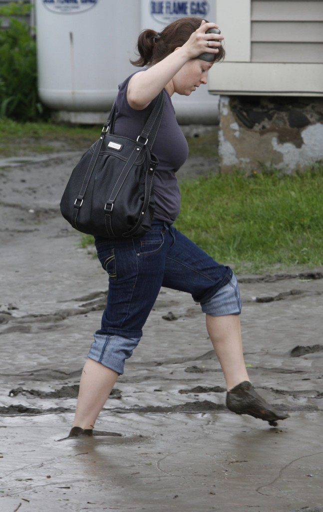 A woman walks on a mud-covered street Friday in Barre, Vt. Roads closed across central Vermont as heavy overnight rains caused rivers to overflow their banks.