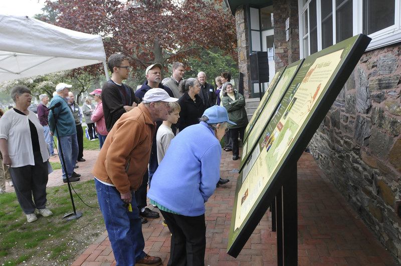 Visitors check out new informational signs that were unveiled at Evergreen Cemetery in Portland on Saturday by the Friends of Evergreen.