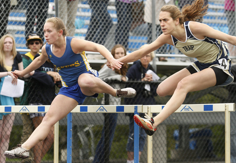Carley O'Brien, right, of Traip Academy focuses on the finish and beats Doe Leckie of Lake Region in the 100-meter hurdles. O'Brien was named best in field events.