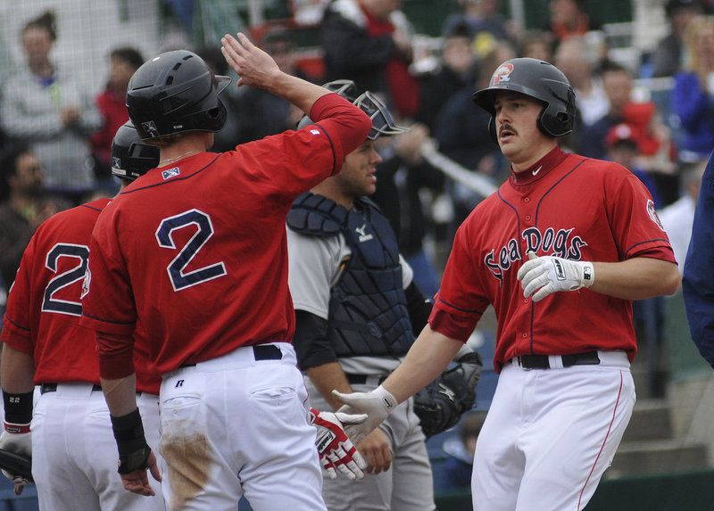 Ryan Lavarnway, right, is greeted at home plate after hitting the first of his two home runs in Portland s 8-7 loss to Trenton in the first game of a doubleheader Saturday at Hadlock Field. The Sea Dogs bounced back to win the second game, 7-5.