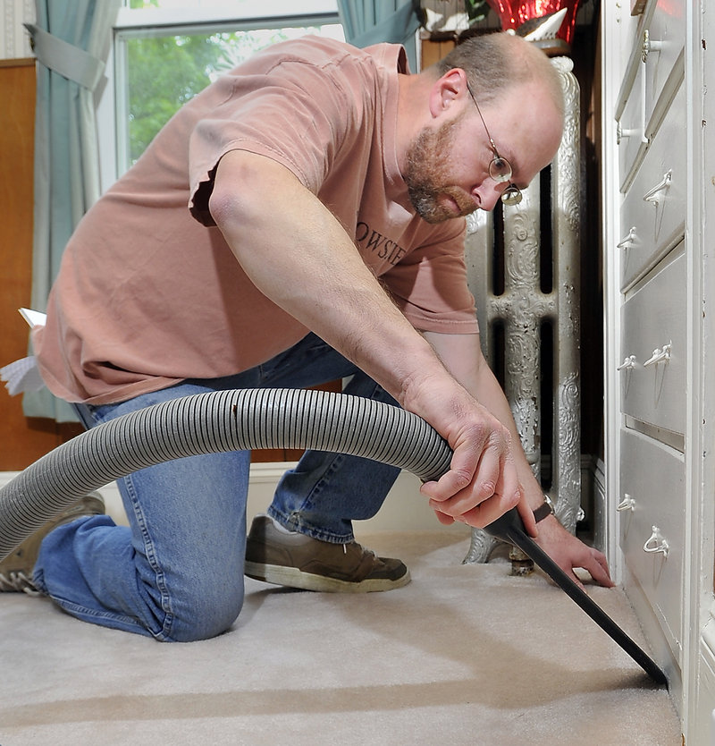 Ray Routhier uses a crevice tool to vacuum the edges before cleaning carpeting with Carpet Services.