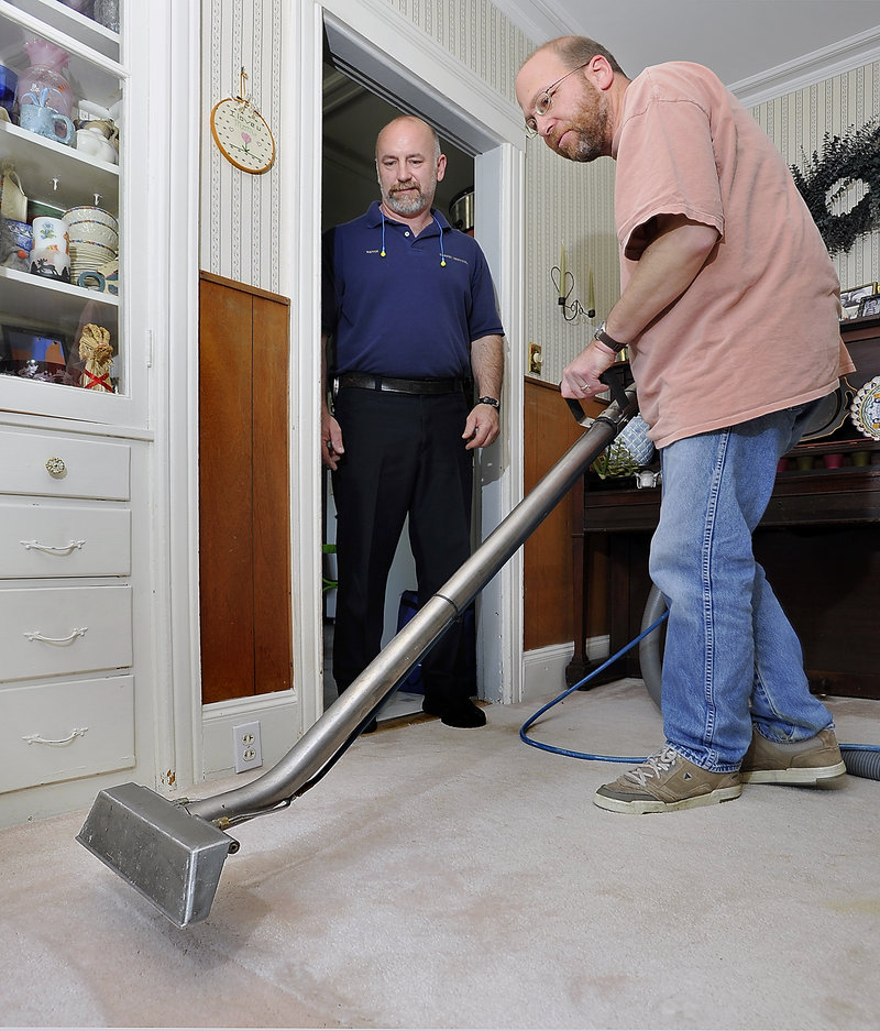 Kevin Burns, left, owner of Carpet Services in Portland, gives guidance to Ray Routhier as he cleans a carpet.