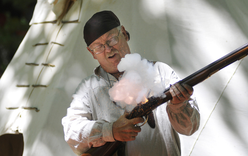 """Ray Hamilton of Livermore demonstrates a """"flash in the pan"""" with a 1776 British flintlock musket. The term refers to gunpowder flaring up without a bullet being fired."""