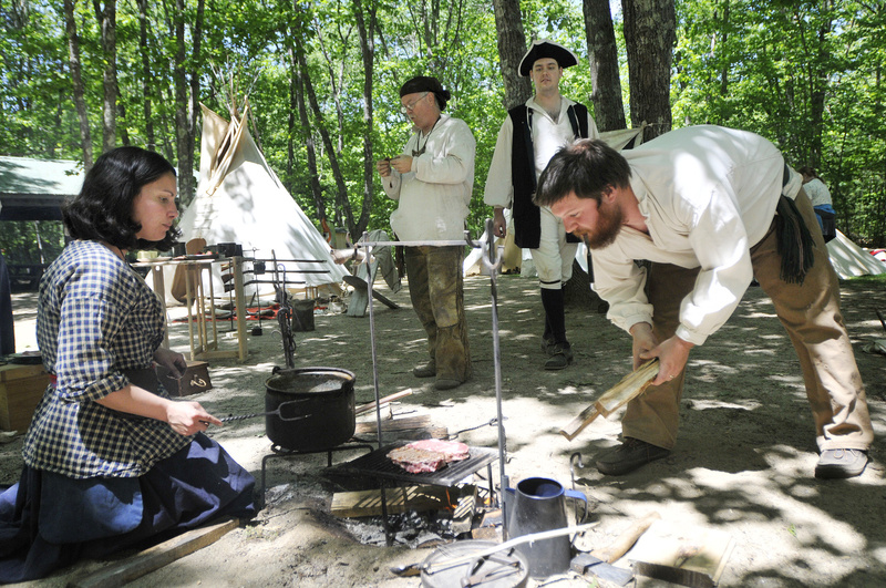 Kurt Priestly of Belmont places split wood on the fire as Renee Grant of Lisbon Falls cooks a steak during the Ancient Ones of Maine camp re-enactment Saturday in Gray.
