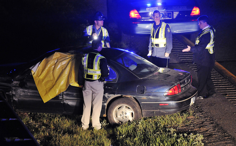 Maine State Police troopers investigate the scene of a crash just off Exit 63 on Interstate 95 late Monday night. Initial reports indicated that the driver killed himself after shooting and killing a Winslow woman and leading police on a chase.