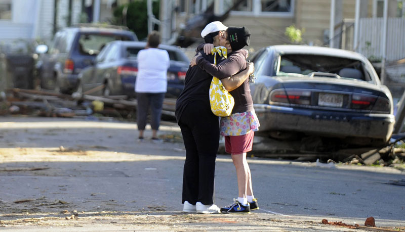 People embrace on a street damaged by Wednesday's tornado in Springfield, Mass., as residents of 19 small communities in central and western Massachusetts were left to deal with widespread damage today.