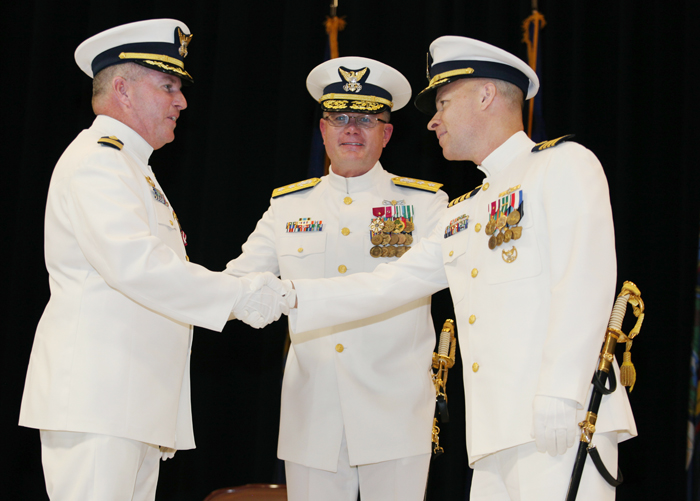 Capt. James McPherson, left, shakes hands with Capt. Christopher Roberge, right, who replaces him as Sector Northern New England commander during a change of command ceremony today in Cape Elizabeth. Rear Adm. Daniel Neptun is at center.