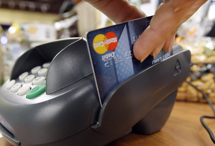 A customer swipes a debit card at checkout at a shop in Seattle.