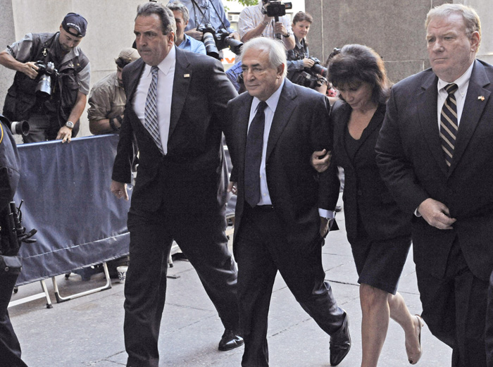 Former International Monetary Fund leader Dominique Strauss-Kahn enters Manhattan criminal court with his wife Anne Sinclair today for his arraignment proceedings on charges of sexually assaulting a hotel maid.