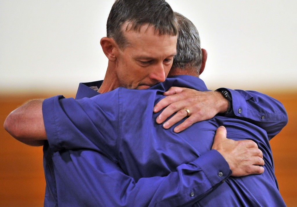 Jeff Bagley hugs his father Ralph Bagley before the funeral for Amy, Coty and Monica Lake at Dexter Regional High School in Dexter on Saturday.