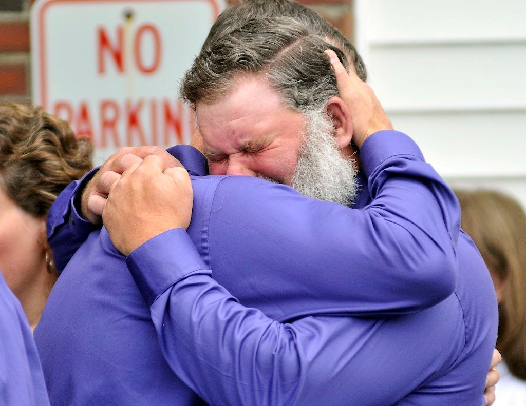 Andrew Higgins, facing, and Jeff Bagley, embrace after the funeral for Amy, Coty and Monica Lake at Dexter Regional High School in Dexter on Saturday. Jeff Bagley is the brother of Amy Lake and Higgins was close friend and pallbearer for the service.