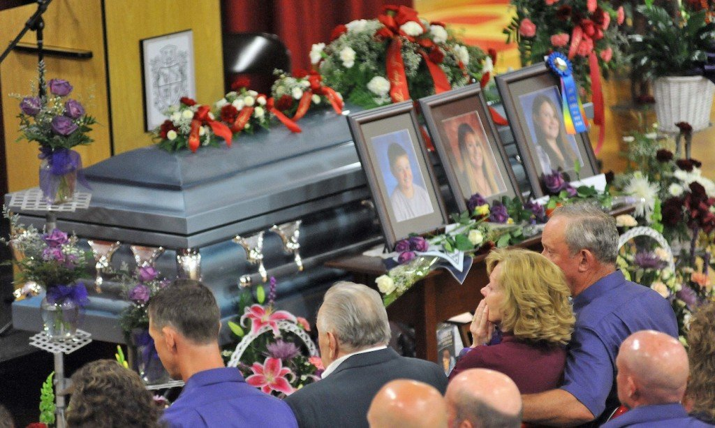 Ralph Bagley, far right, holds his wife Linda as they sit in front of the casket that holds their daughter Amy and grandchildren, Coty and Monica, during the funeral at Dexter Regional High School on Saturday.
