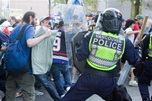 Police stand in front of people on the street following Game 7 of the NHL hockey Stanley Cup Finals between the Vancouver Canucks and the Boston Bruins on Wednesday, June 15, 2011, in Vancouver, British Columbia. (AP Photo/The Canadian Press, Geoff Howe) CANUCKS BRUINS CANADA CANADIAN BRITISH COLUMBIA B.C. SPORTS PLAY ICE HOCKEY GAME ACTION COMPETITIVE COMPETITION COMPETE ATHLETICS ATHLETE NHL NATIONAL HOCKEY LEAGUE PLAYOFFS PLAYOFF FINAL FINALS STANLEY CUP