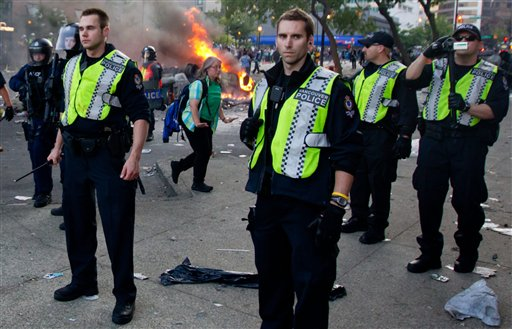 Police officers stand together after rioters burned police cars following the Vancouver Canucks being defeated by the Boston Bruins in the NHL Stanley Cup Final in Vancouver, British Columbia, Wednesday, June 15, 2011. Angry, drunken revelers ran wild Wednesday night after the Vancouver Canucks' 4-0 loss to Boston in Game 7 of the Stanley Cup finals, setting cars and garbage cans ablaze, smashing windows, showering giant TV screens with beer bottles and dancing atop overturned vehicles. (AP Photo/The Canadian Press, Darryl Dyck) CANADA CANADIAN BRITISH COLUMBIA B.C. VANCOUVER