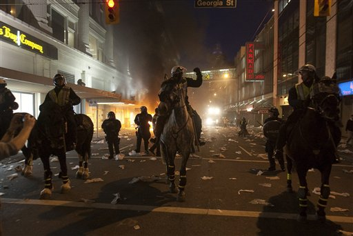Police on horseback move down a street during a riot following the Vancouver Canucks being defeated by the Boston Bruins in the NHL Stanley Cup Final in Vancouver, British Columbia, Wednesday, June 15, 2011. Angry, drunken revelers ran wild Wednesday night after the Vancouver Canucks' 4-0 loss to Boston in Game 7 of the Stanley Cup finals, setting cars and garbage cans ablaze, smashing windows, showering giant TV screens with beer bottles and dancing atop overturned vehicles. (AP Photo/The Canadian Press, Ryan Remiorz) CANADA CANADIAN BRITISH COLUMBIA B.C. SPORTS PLAY ICE HOCKEY GAME ACTION COMPETITIVE COMPETITION COMPETE ATHLETICS ATHLETE NHL NATIONAL HOCKEY LEAGUE PLAYOFFS PLAYOFF WESTERN CONFERENCE SEMIFINAL STANLEY CUP
