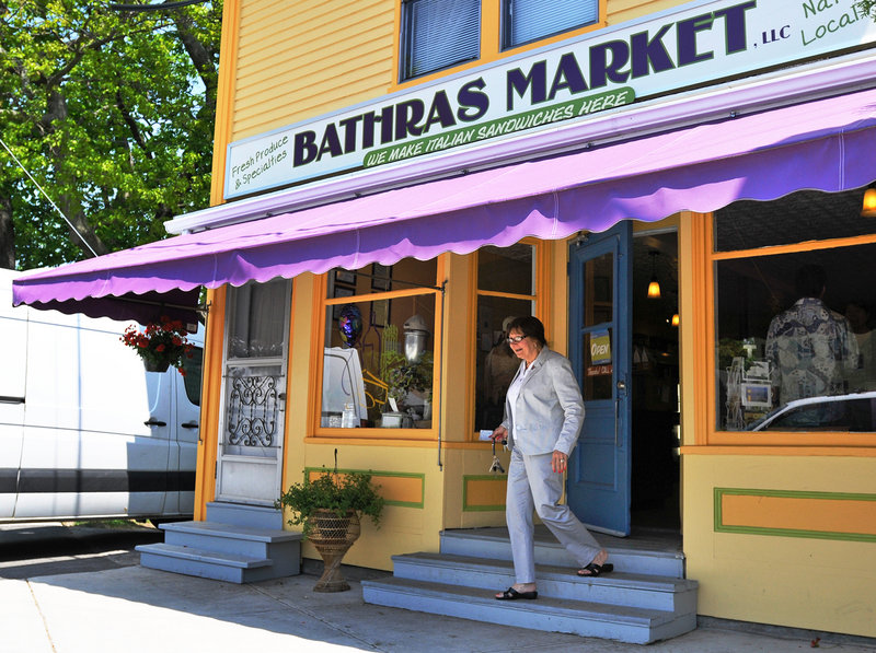 A patron exits Bathras Market in Willard Square in South Portland. The market has recently reopened.