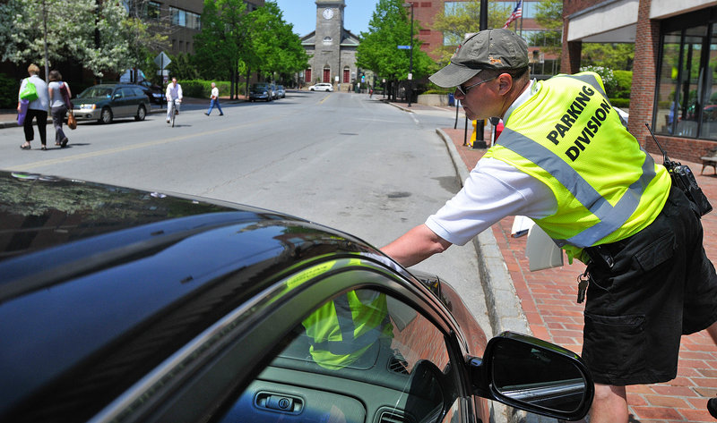 Parking Control Officer Chuck Fagone tickets a car for an expired meter on Temple Street in Portland. Ending the ticket forgiveness program appears to have helped the city's bottom line, seemingly without a massive negative impact on visitor traffic.