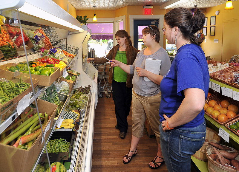 Marada, left, and Leah Cook, right, who are launching a company to process Maine-grown organic vegetables, talk to Kate Bathras, center, manager of Bathras Market in South Portland, about products from their organic food delivery service.