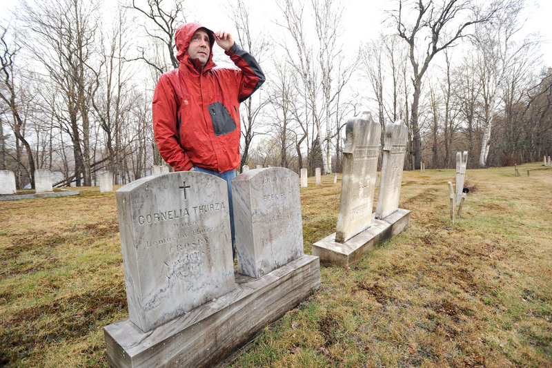 "Ben Godsoe of the High Peaks Alliance land trust is leading an effort to build a 45-mile trail between Strong and Oquossoc that marks the places where Cornelia ""Fly Rod"" Crosby fished and worked. Here, he stands beside Crosby's grave at the start of the trail in Strong."