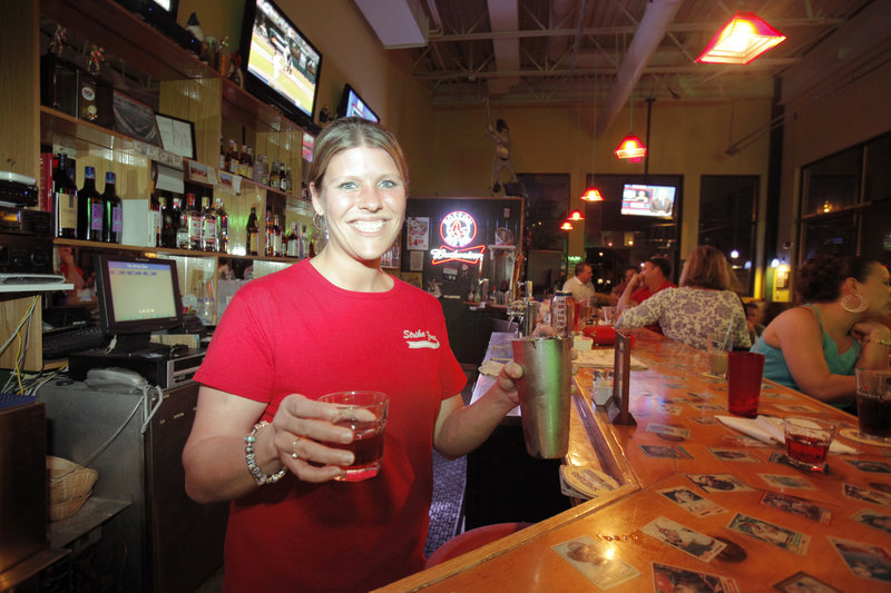 Allyson Carter, manager of The Strike Zone in Old Orchard Beach, pours a Washington Apple, which is made with Crown Royal, Apple Pucker and cranberry juice. The sports bar is on the main street downtown.