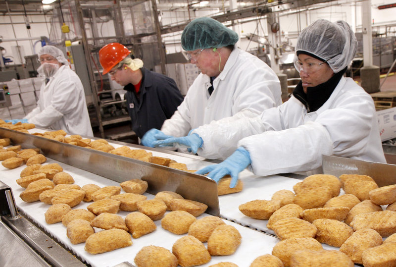 Barber Foods workers sort frozen chicken products Wednesday in the Portland plant, which will remain open. But production lines will be consolidated and the work force reduced.
