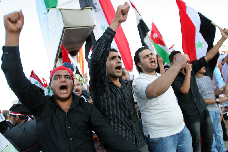 Protesters waving Syrian and Jordanian flags demand the resignation of Syrian President Bashar Assad, in Amman, Jordan, on Wednesday. Images of children killed in a government crackdown are circulating on YouTube, Al-Jazeera, Facebook and opposition websites.
