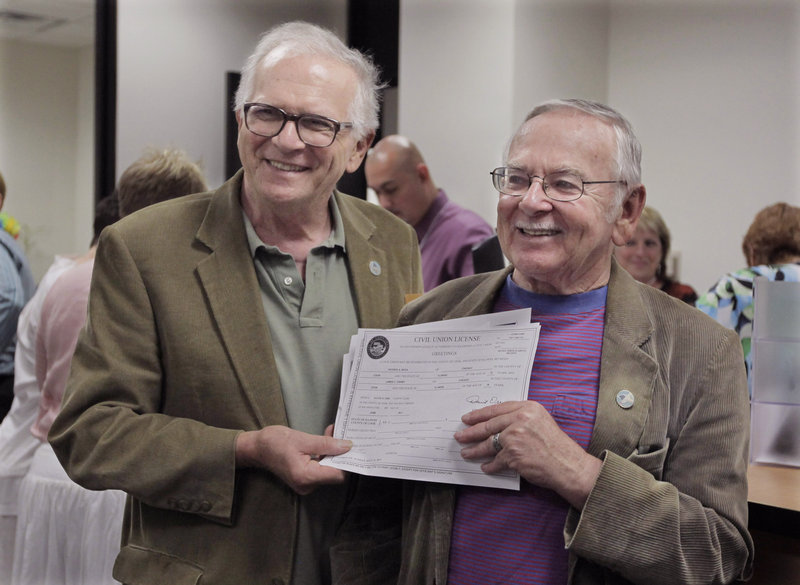 Patrick Bora, 73, left, and his partner Jim Darby, 79, show off their civil union license at the Cook County Office of Vital Records Wednesday in Chicago. The couple arrived early in the morning to be in line as Illinois' new civil union law took effect.